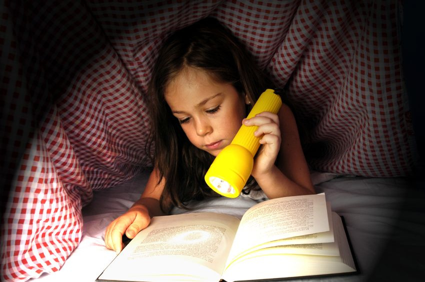 girl reading with flashlight