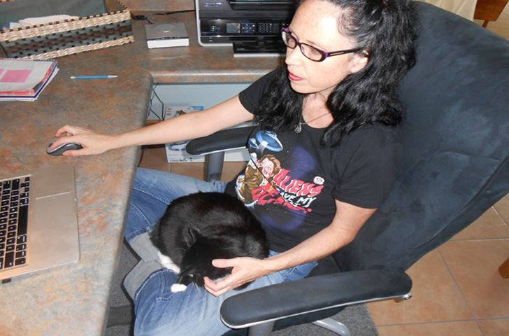 angie writing propsal with cosmo in lap