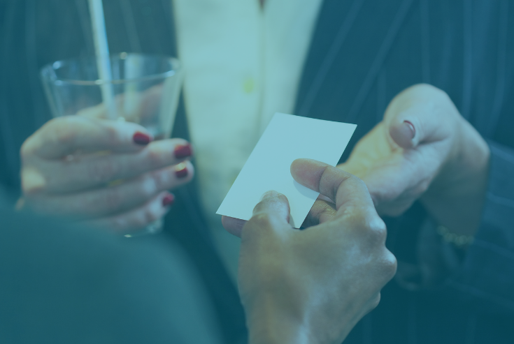 Two women exchanging a business card with heading How to Successfully Network at an In-person Event
